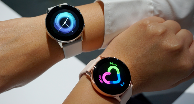two samsung watches displayed on wrists