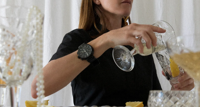 lady pouring drink and wearing boyfriend watch