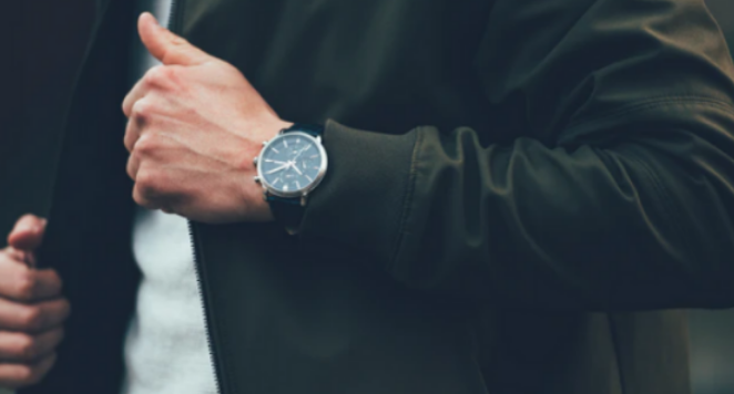 Man wearing suit with aviator watch on wrist