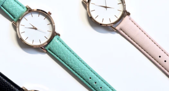 a 90s watch with a light blue strap beside a 90s watch with a light pink strap