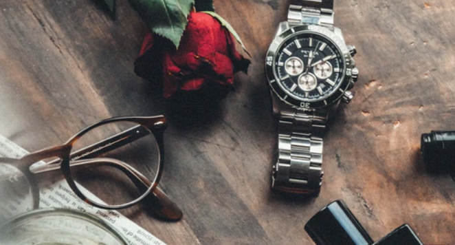 watch on a wooden table with a rose and a pair of glasses