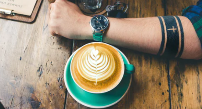 tattooed man wearing watch at a cafe