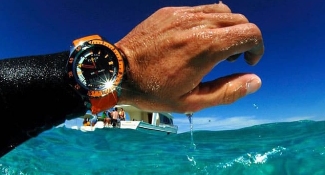 Black and orange dive watch in the sea