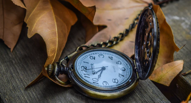 vintage pocket watch surrounded by autumn leaves