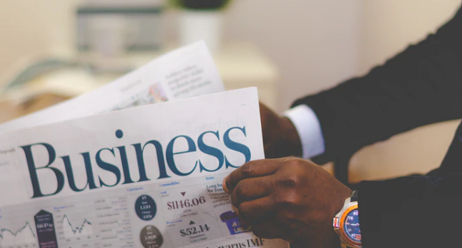 man reading a business newspaper and wearing a colourful watch