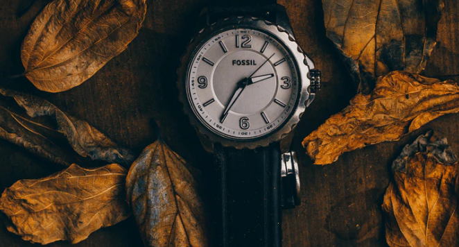 Fossil watch with autumn leaves in background