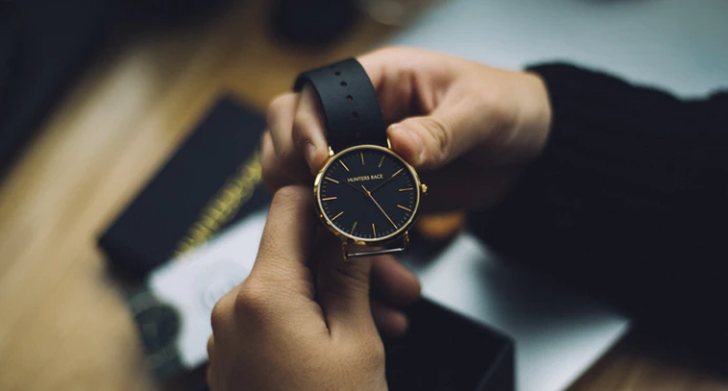 man holding black dial men's watch