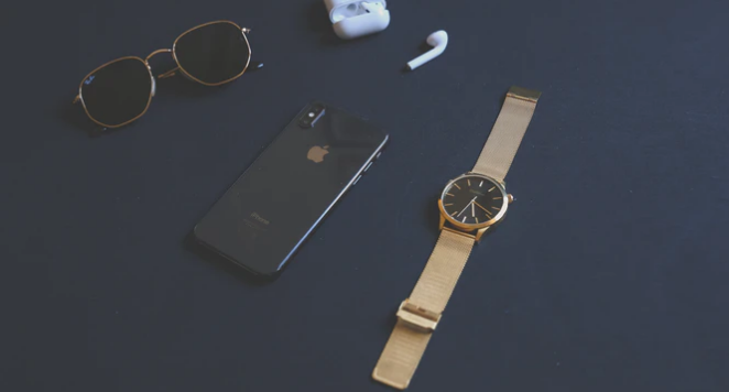 watch with gold strap placed next to accessories against a blue background