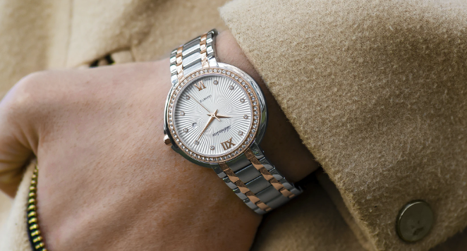 woman wearing camel coloured coat and dual toned rose gold and silver watch with metal bracelet